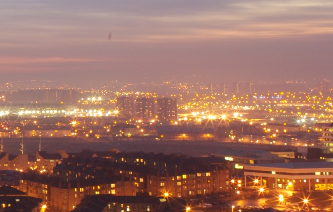 View of the lights of a city at sunset