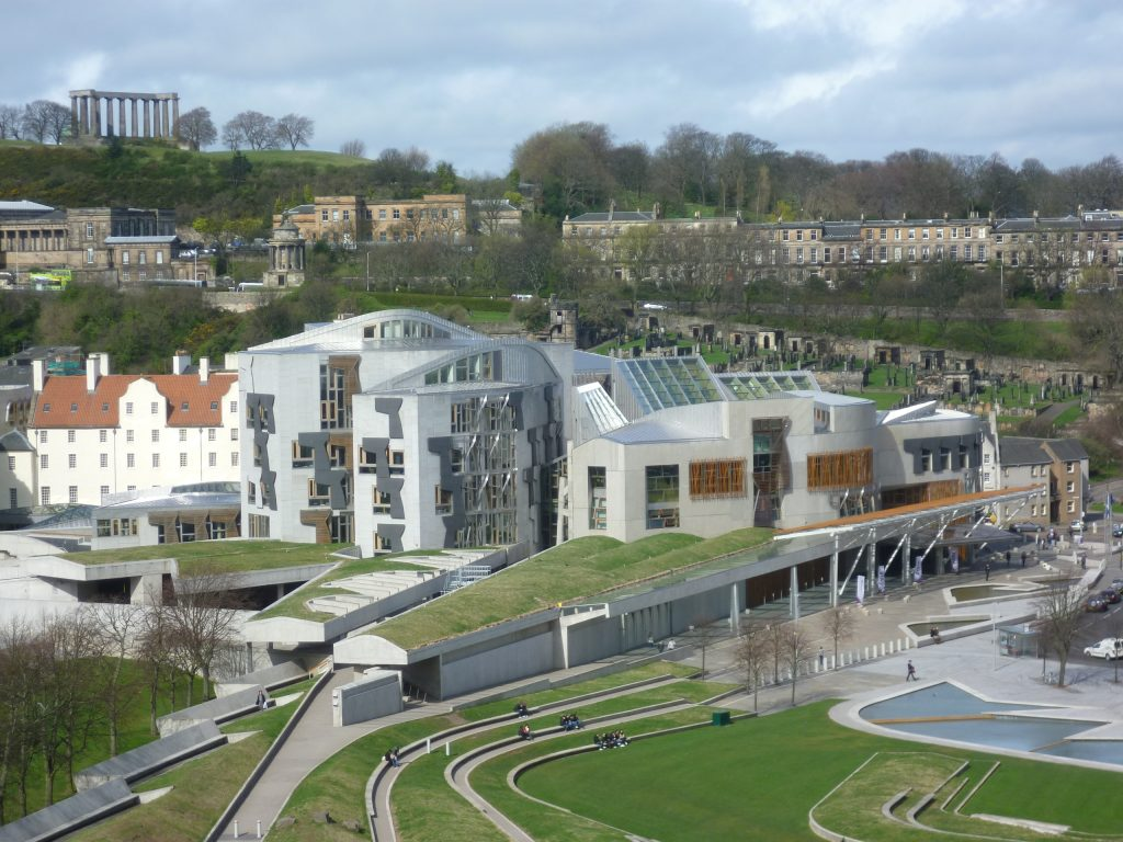 A view of the Scottish Parliament building  in Edinburgh with Calton Hill behind it.