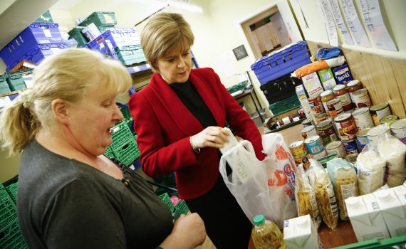 Two women stand in front of a table with carrier bags full of food.