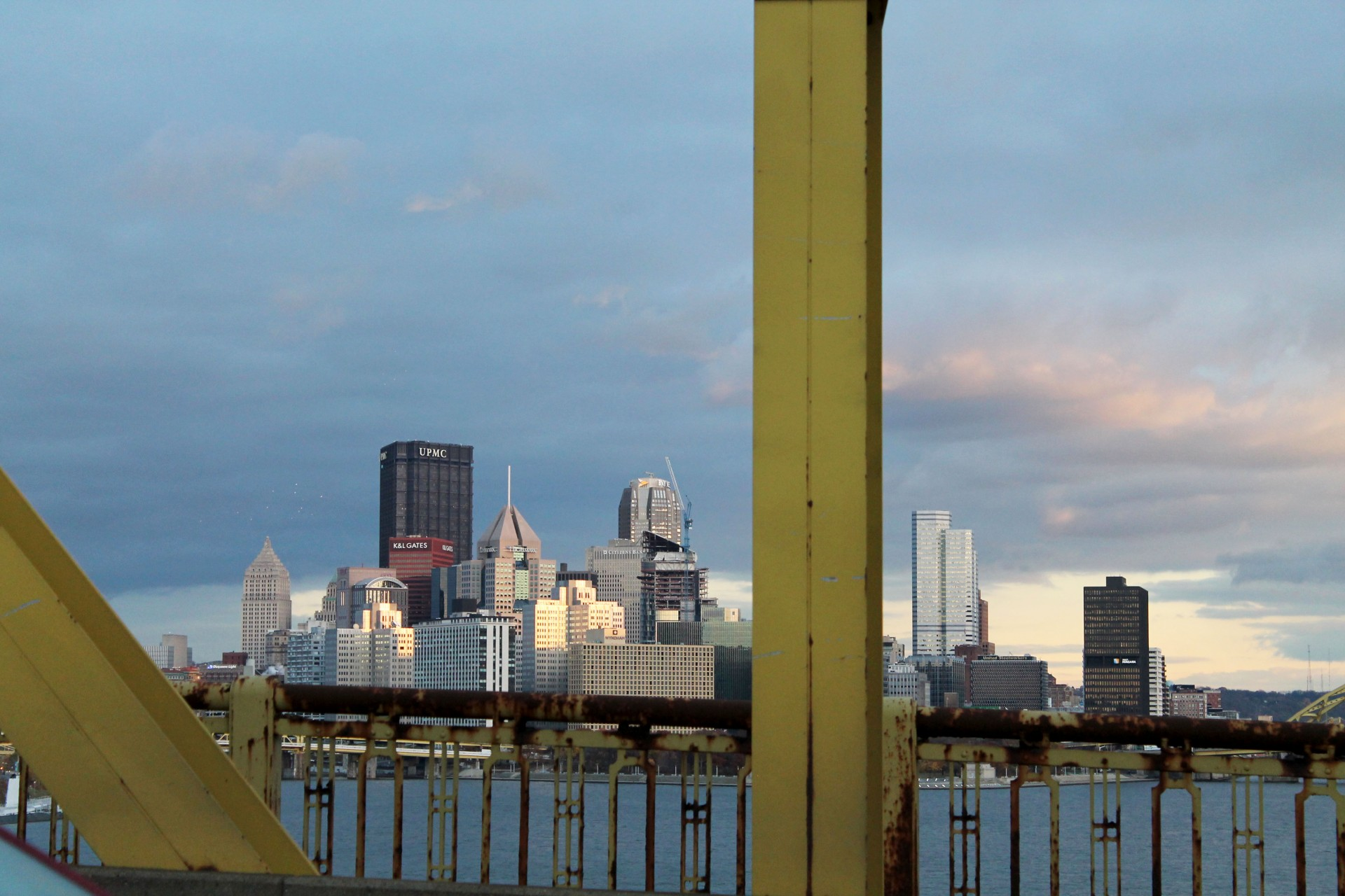 View of city skyline with rusty railings and metal girders in foreground