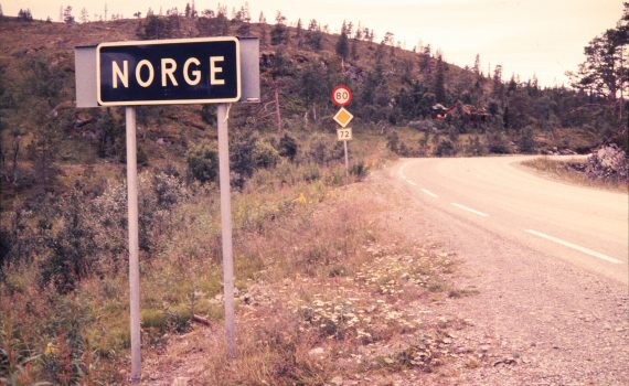 "A road bends sharply off to the right, with trees on either side. A sign in the foreground reads ""NORGE""."