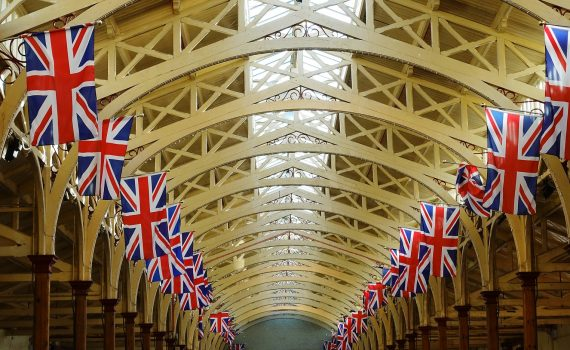 The internal roof of a marketplace, with rows of Union Jack flags lining either side.