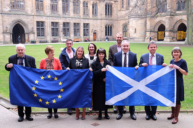 People holiding the EU and Scottish flags