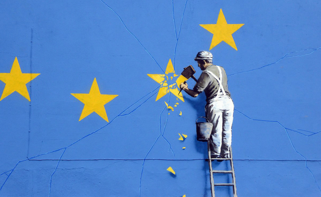 man with hammer chipping at the EU flag to demonstrate Brexit