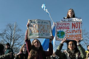 """Teenage girls at the Fridays for Future Climate Strike in Edinburgh in March 2019. Their signs read 'System Change, not Climate Change' and '""""Act as if the house is on fire. Because it is."""" Greta Thunberg'"""