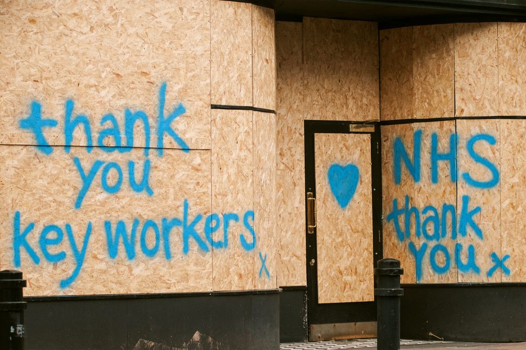 A boarded up shop on which is grafitti saying 'Thank you key workers x', a heart, and 'NHS thank you x'