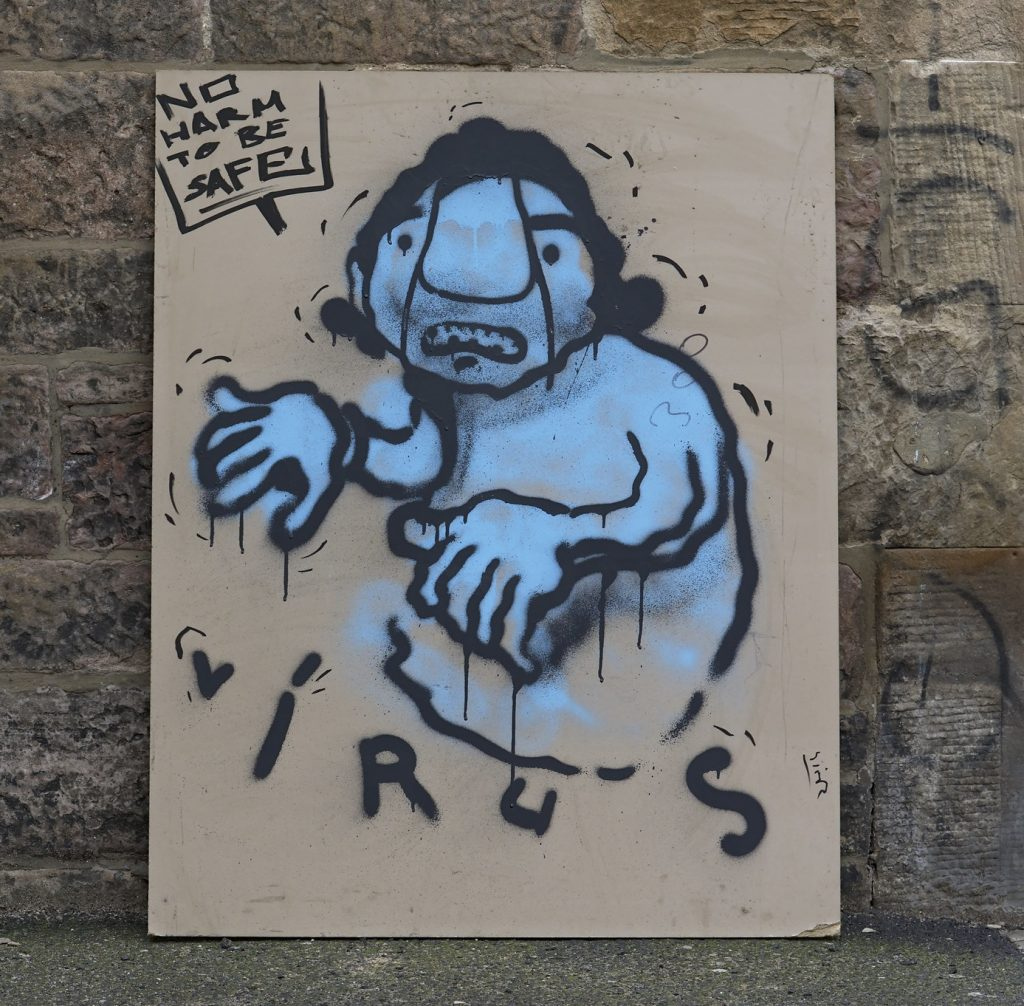 A cartoon painted on a board leaning against a wall. It shows a person who is blue and shivering with the word 'virus' underneath them, and the words 'No harm to be safe' written in a box at above figure.