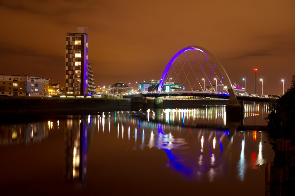 a view at night across the river Clyde with the Clyde Arc bridge and buildings behind, all lit up