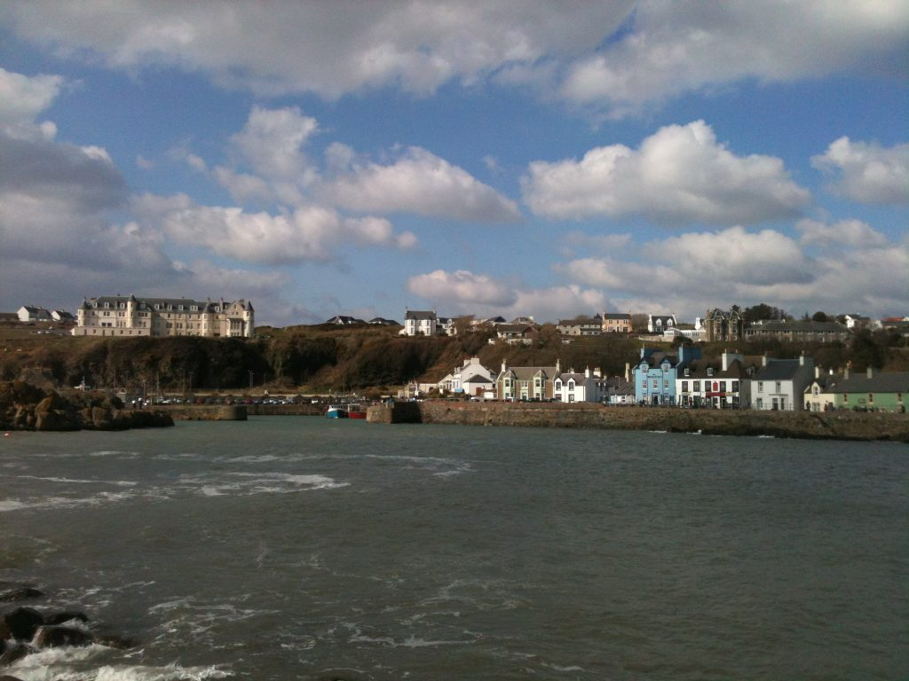 View of part of the town of Portpatrick from across the harbour with white and blue painted buildings along the harbour road and a large Victorian hotel on the clifftop