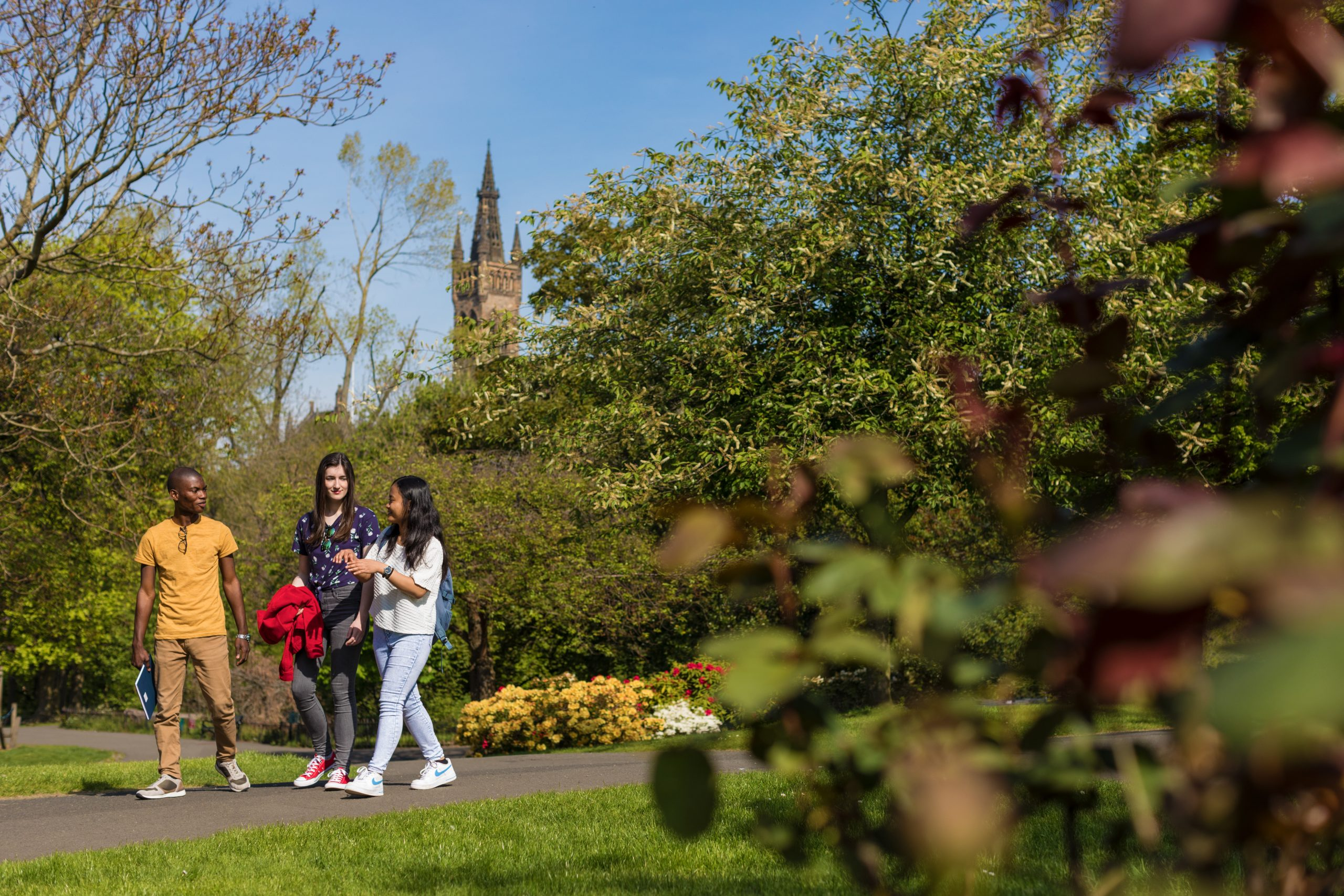 Three postgraduate students walking in Kelvingrove Park on sunny day surrounded by trees, grass and flowers and with the University tower behind them