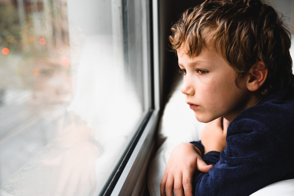 Face of a boy lying on his front and gazing out of a window