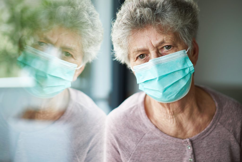 An older woman wearing a medical mask and leaning against a window, where there is some greenery