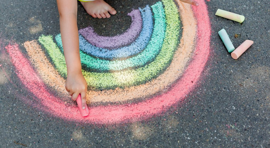 A child's hand holding a pink piece of chalk as she completes drawing a rainbow on the tarmac