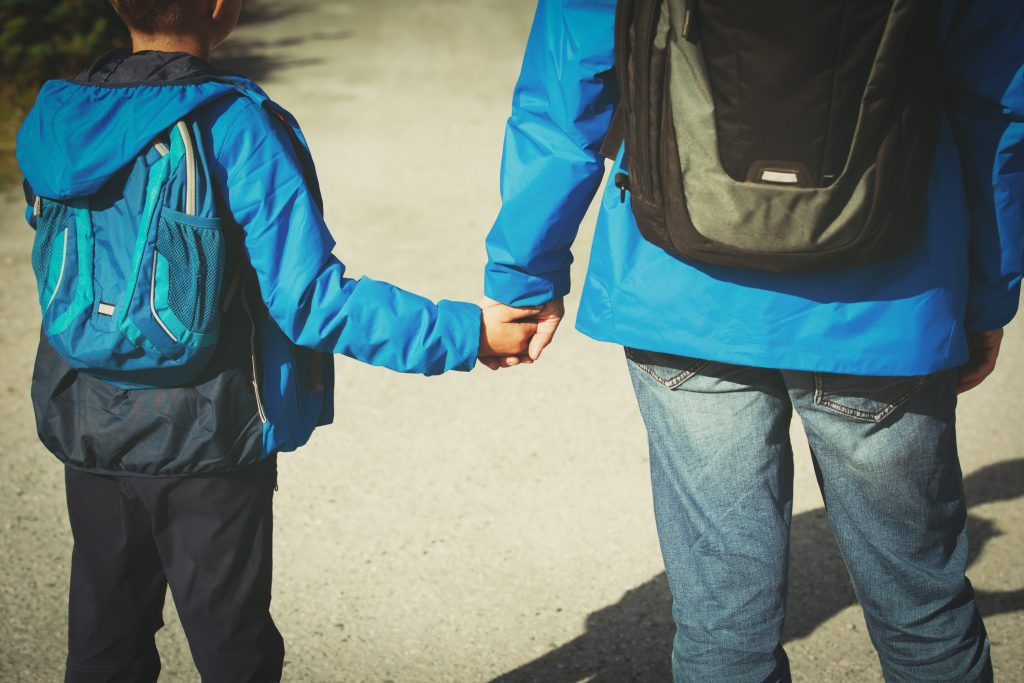 Photos showing a child and father from behind wearing anoraks, jeans and backpacks. The father is holding the boy's hand