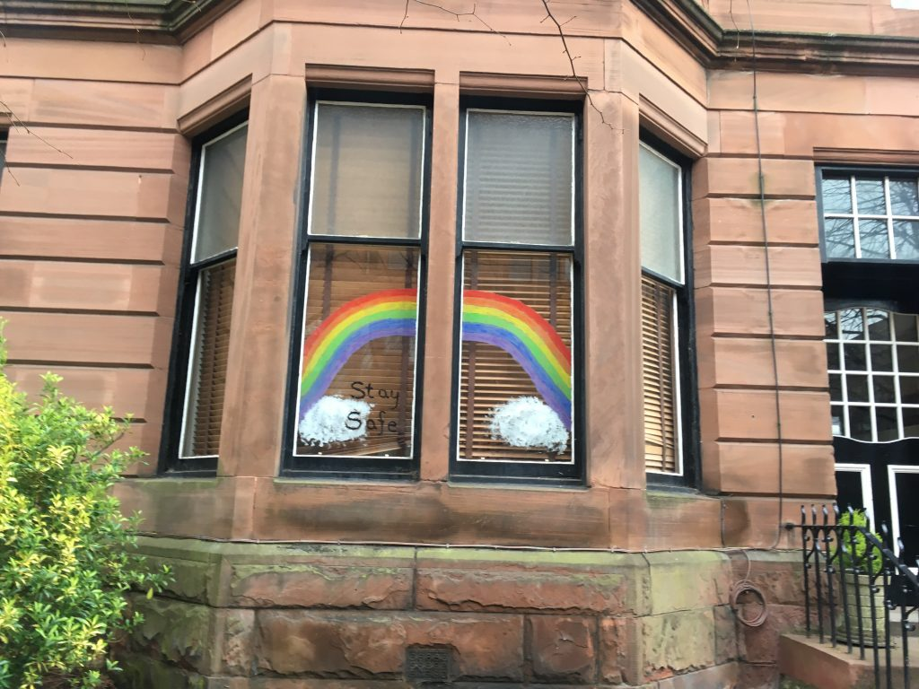 Rainbows and clouds painted onto a bay window with the words stay safe