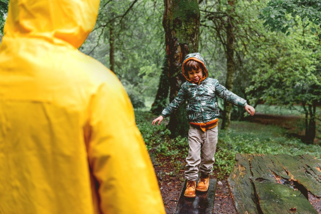 A young boy balancing to walk along a log towards an adult on a rainy day in the woods
