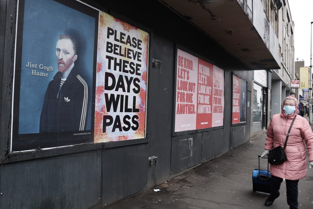 Elderly woman with a medical mask walking past COVID posters on a boarded up shop in Glasgow wearing. The posters say 'Jist Gogh Hame' (with a modernised portrait of Van Gogh), 'Please Believe These Days Will Pass' and 'Be Kind, Let''s Look Out for One Another'.