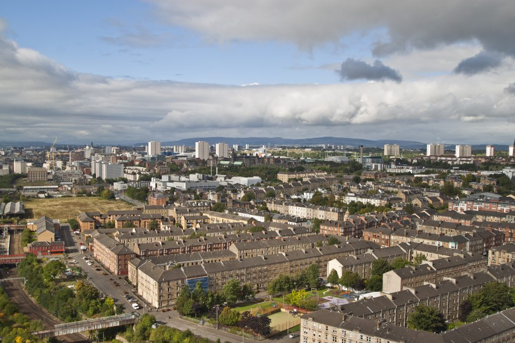 View of Glasgow with tenements, modern tower blocks, a train line and industrial buildings and hills in the distance