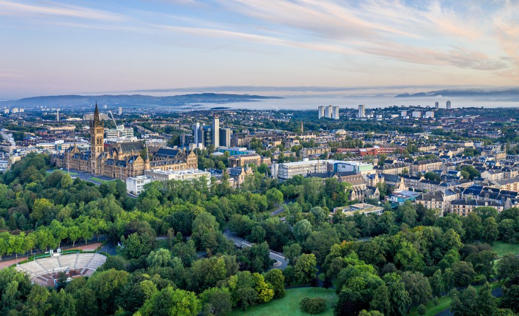 Aerial view of Glasgow including Kelvingrove Park and Glasgow University in the foreground looking over the North and West of the city with tenements and tower blocks with hills visible in the distance.