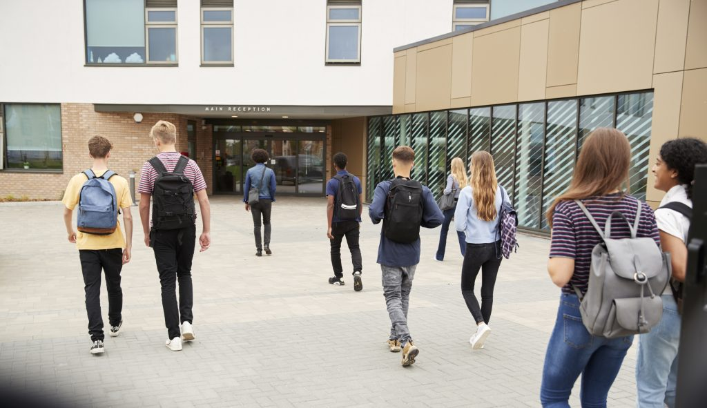 Teenagers seen from the back walking towards the entrance for their school.