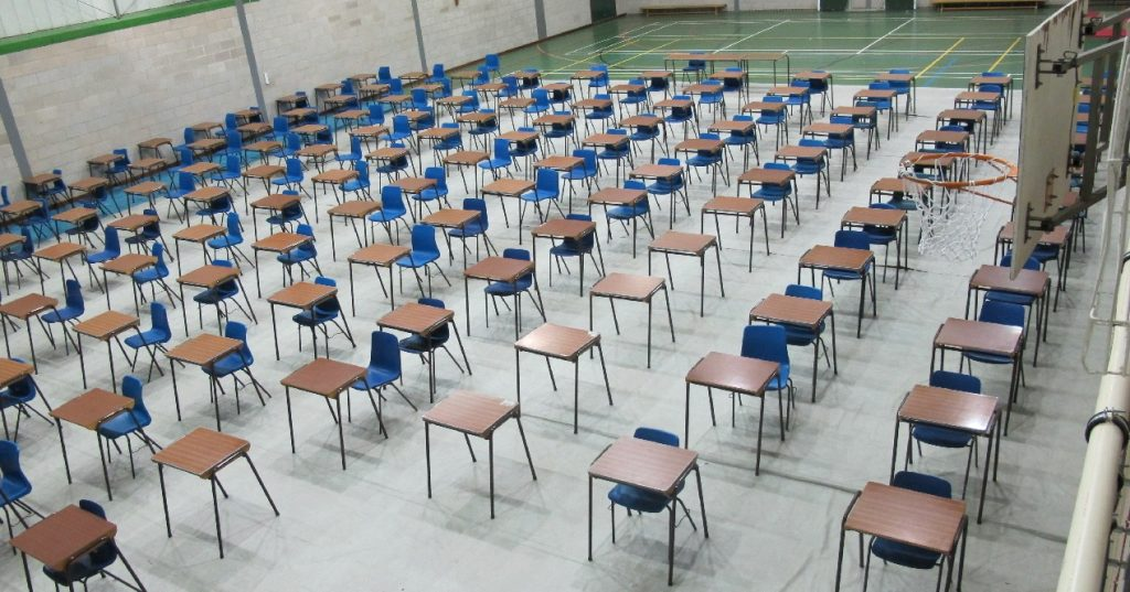 School sports hall seen from a high angle with rows of individual tables and chairs set out for pupils to sit exams