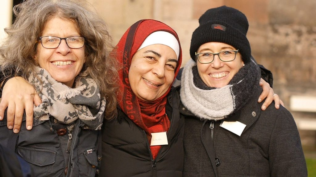 Three women in a close group wearing jackets, scarves and hats. The central woman is wearing a hijab