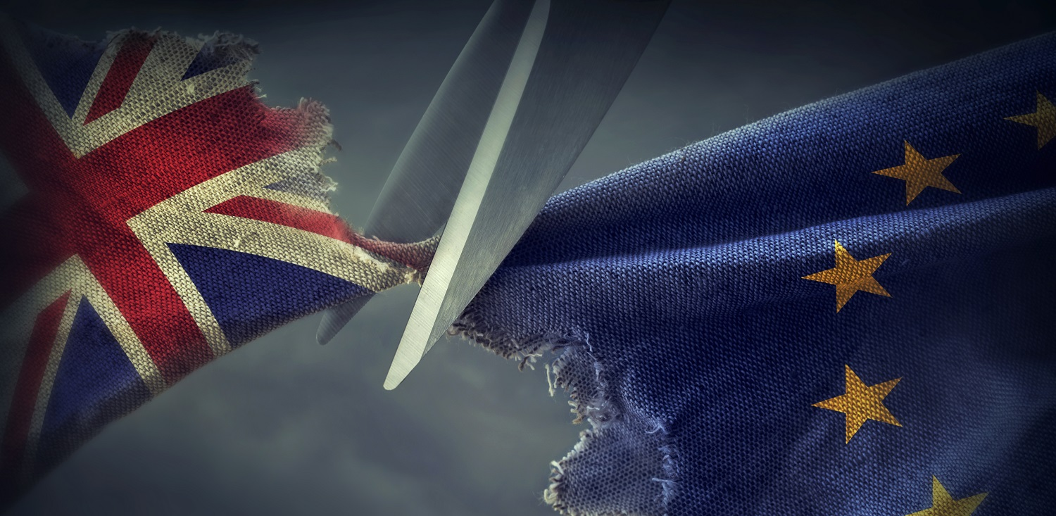 A pair of scissors separating two pieces of fabric whcih are tearing apart - one is the British union flag, the other is the European Union flag