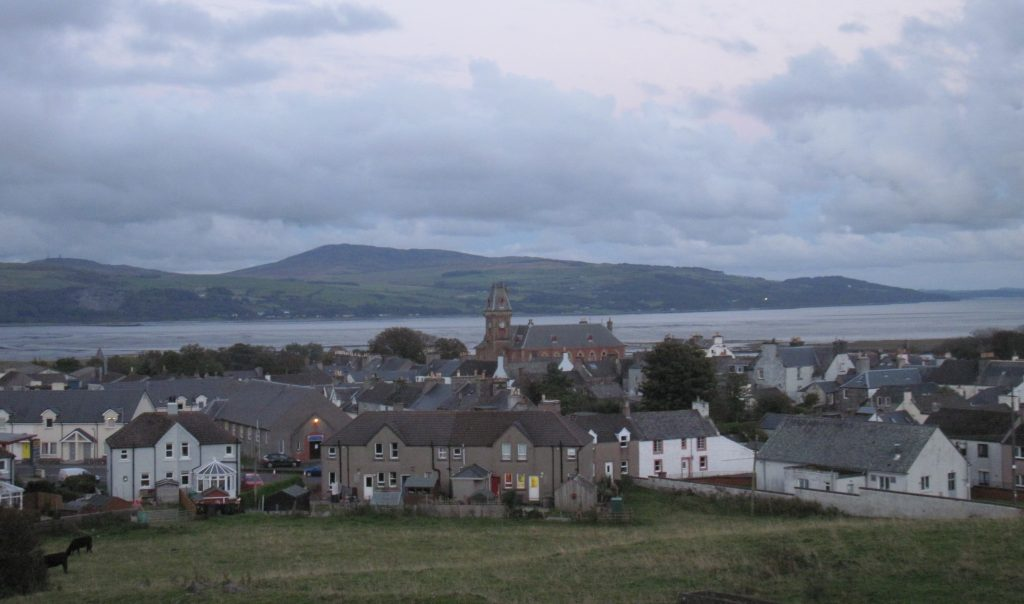 View of a small town with mid-20th century houses, older properties and a Victiorian town hall. Behind the town is a sea loch and more hills