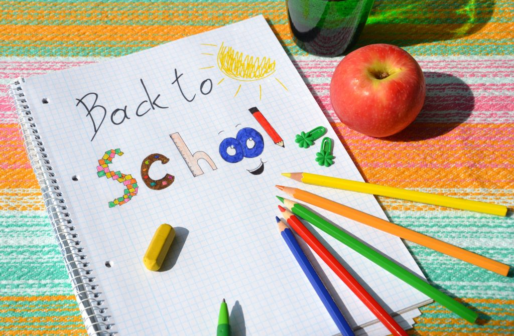 A school notepad with 'Back to School' written on it, with crayons, coloured pencils and an apple