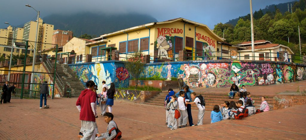 Primary age children talking and playing in the playground of a school in Bogota with colourful grafitti on the wall behind them
