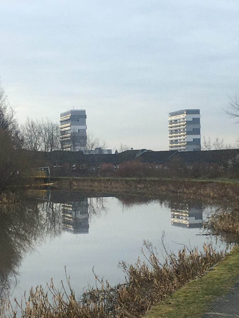 View of the bend in a canal with red brick houses just the other side of the towpath and then two tower blocks in the distance which are reflected in the water