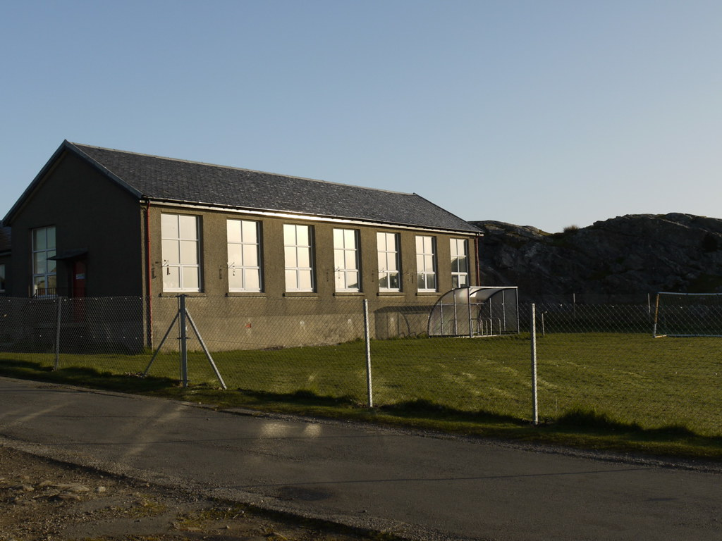 Photo of a small grey school building in the sunshine, with small hills behind