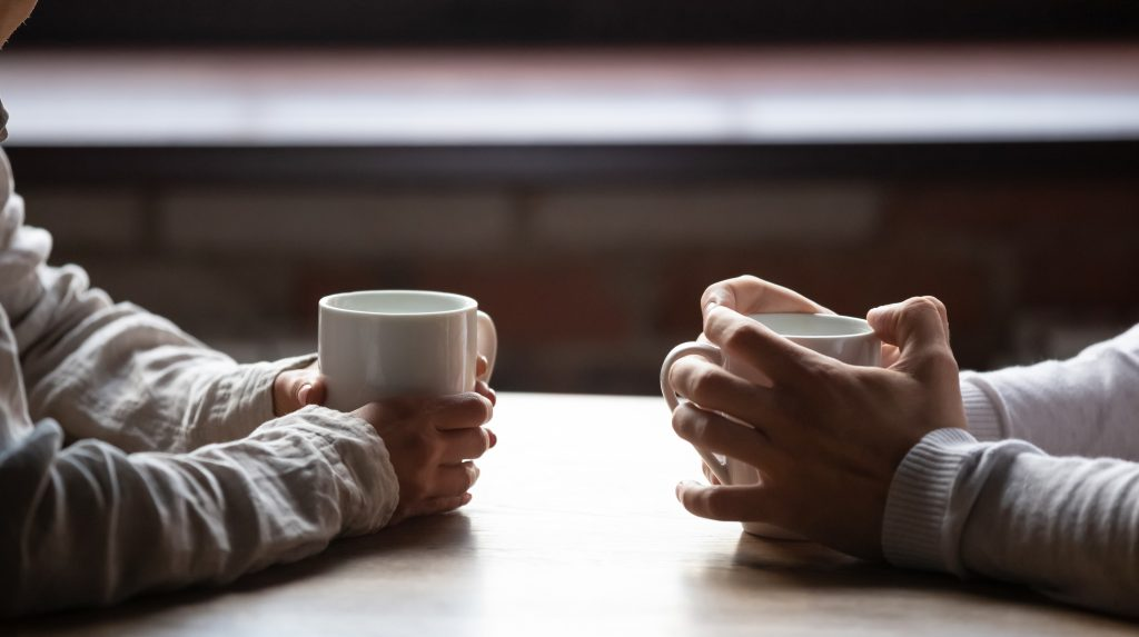 The hands of two people sitting opposite each other at a table each holding mugs of tea or coffee.