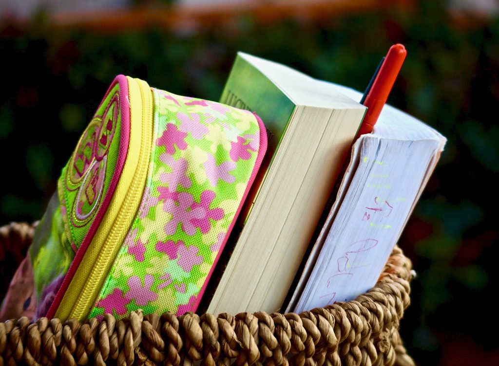 A basket with a small brightly coloured and patterned backpack two books, and a pen