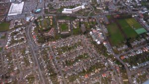 An arial view of streets with houses, buildings and green space