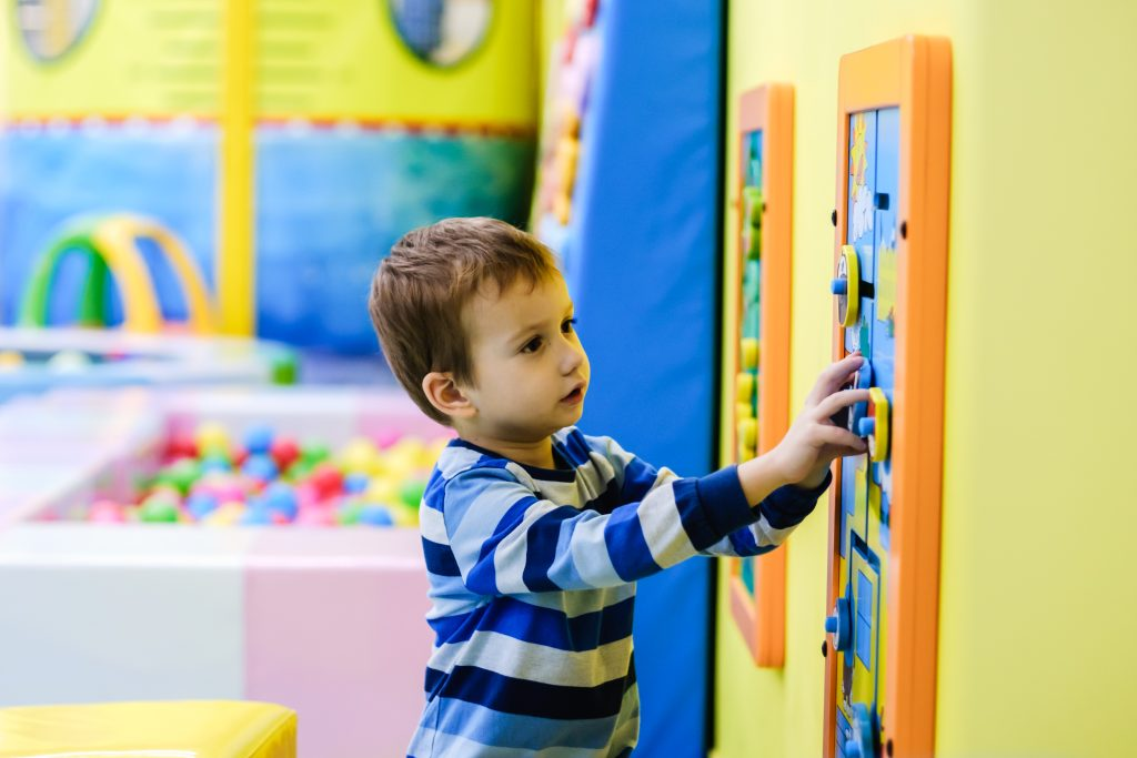 A little boy playing with pictures and shapes on a board on the wall in a learning centre