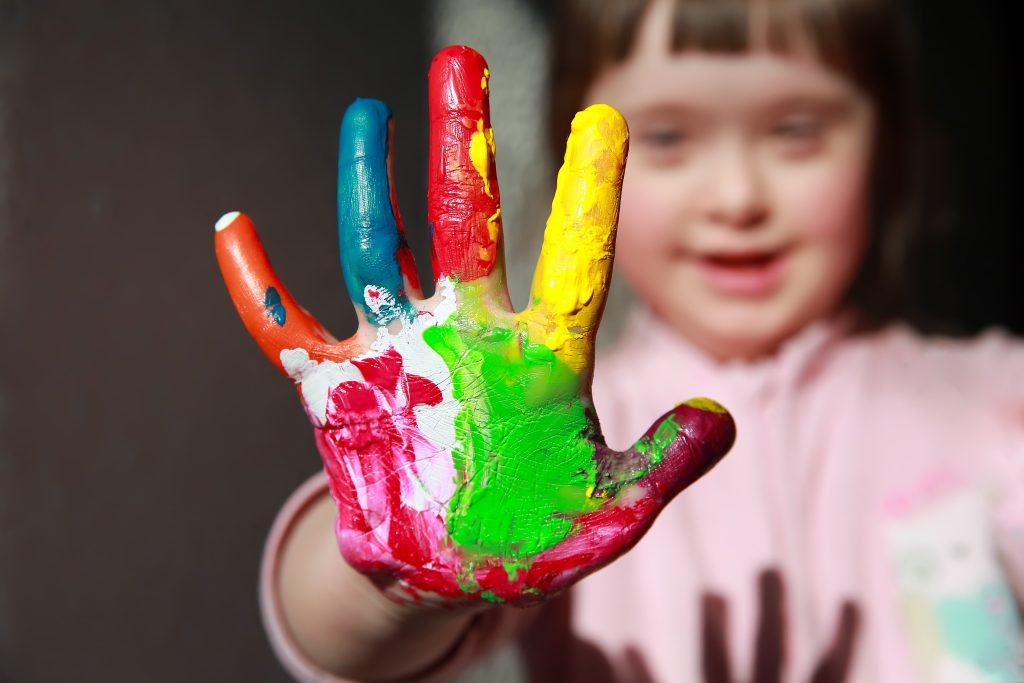 A young girl - not in focus but smiling - stretches out her hand to camera: her fingers and palm are daubed with patches of different coloured paint
