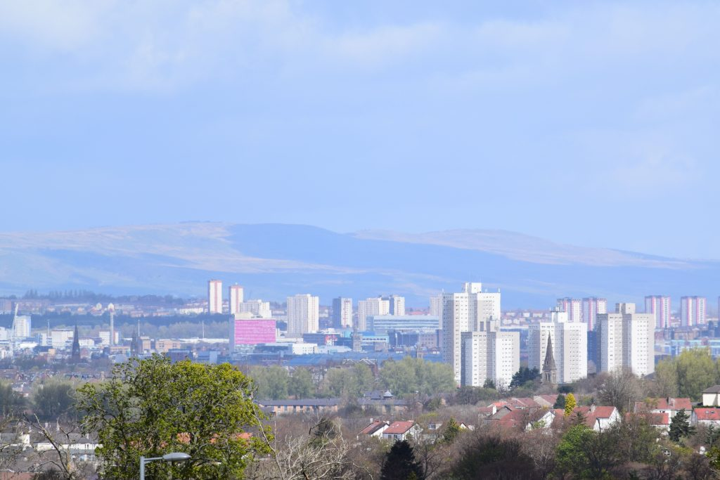 Cityscape view over the west of Glasgow city and suburbs wirth houses, tower blocks, church spires, office buildings, and hills beyond the city