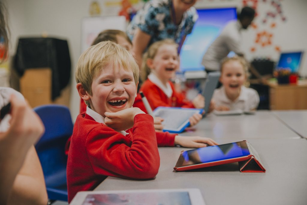 Happy little boy is smiling for the camera while using a digital tablet in his technology lesson at school