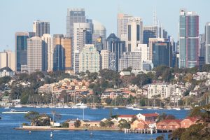 View across Sydney Harbour with small houses and apartments near the shore and tall modern office blocks behind them