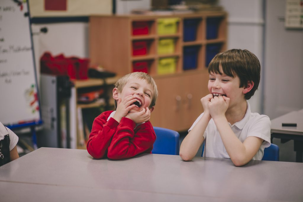 Two young boys sitting at a table in a classroom and laughing with each other