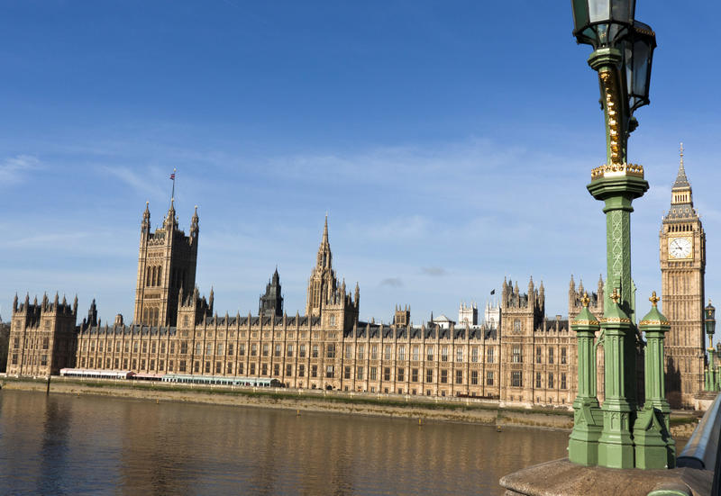 A view of the UK Houses of Parliament and the tower of Big Ben on a sunny day from a bridge over the River Thames