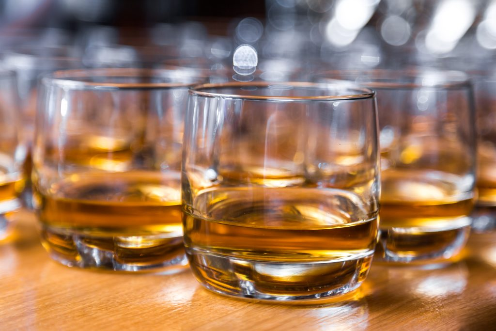 Close-up of tumbler glasses of whisky on a table