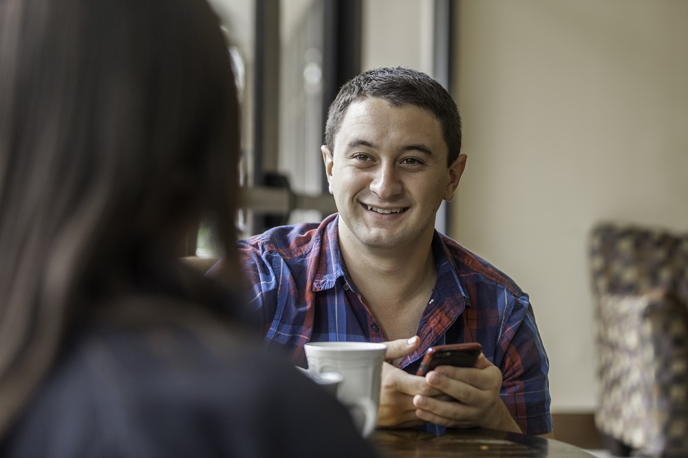 Man holding his phone and having a discussion with a woman seen from the back who is drinking tea or coffee