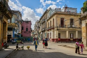 A street of old buildings in Cuba with some people
