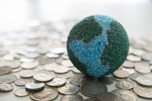A small handpainted globe sitting on some coins