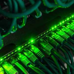 Close-up of lots of green network cables connected to black switches glowing under green lights in the dark
