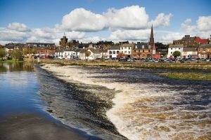 Old buildings in Dumfries see across a river weir