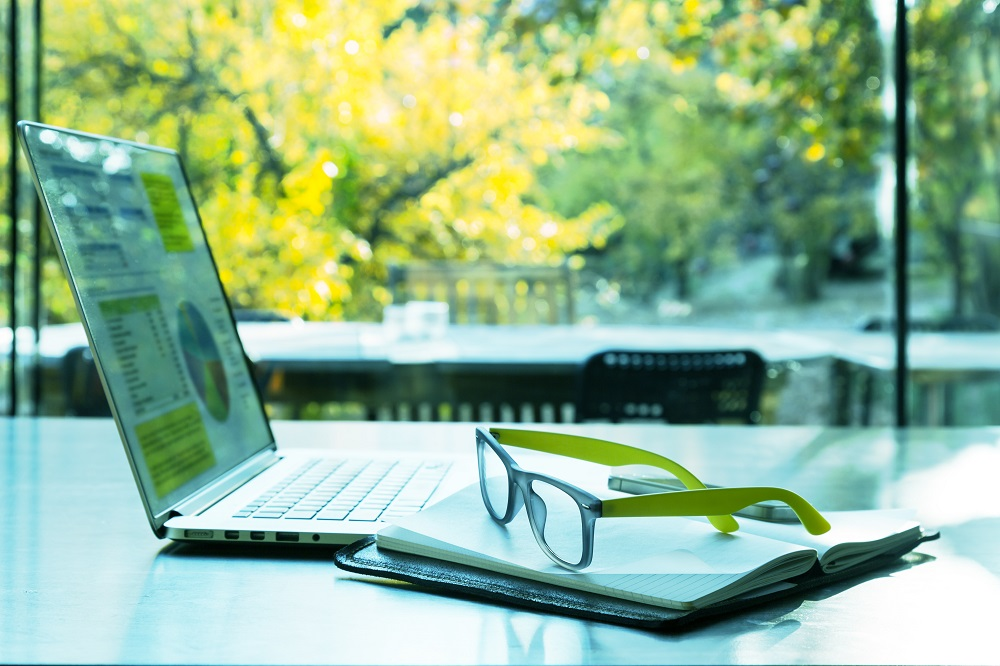 A laptop open on a desk with a notepad, phone and pair of glasses. Beyond the desk is a window with trees outside