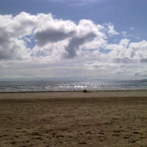 A sandy beach with a few people, with the sea beyond it and the horzion to the blue sky which has some fluffy white clouds